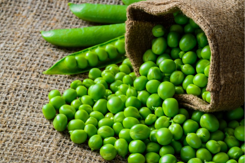 A bag of peas and some peapods on a cloth surface.
