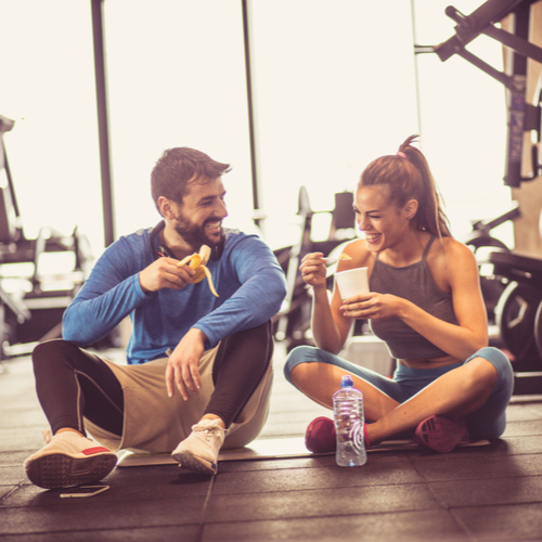 A couple at the gym having snacks after working out.