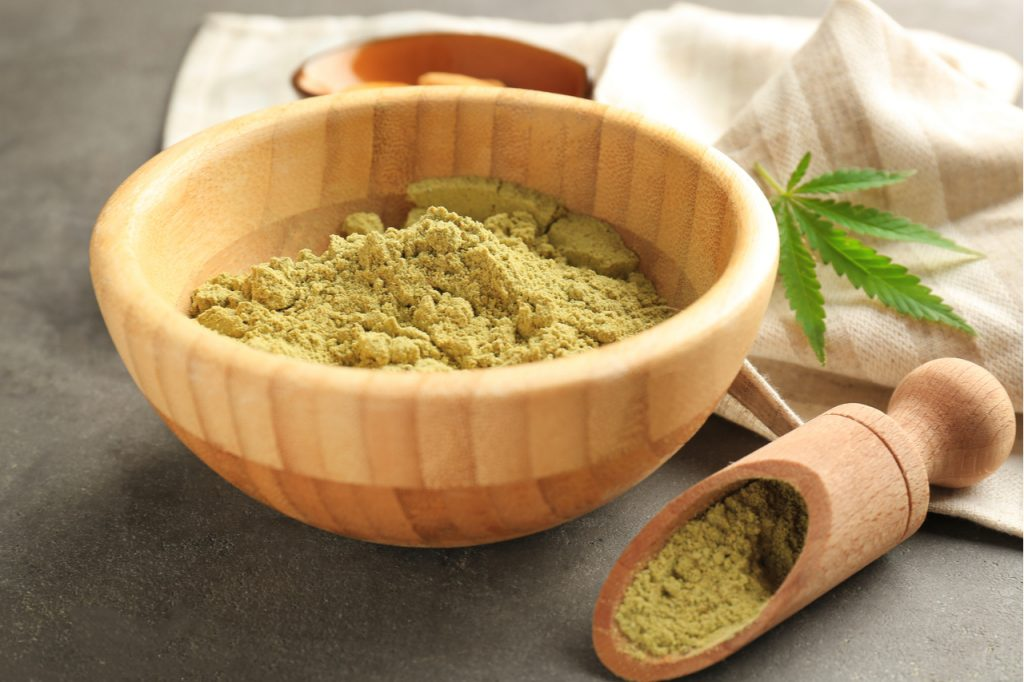 Hemp protein powder in a wooden bowl with a leaf of cannabis on the side.
