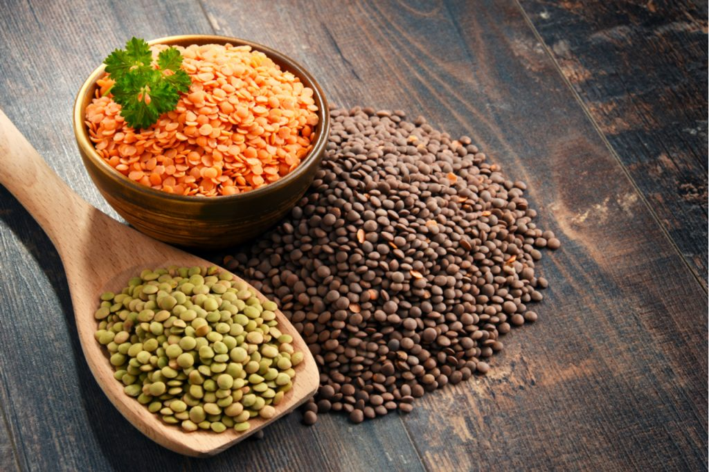 Different types of protein-rich lentils, in a bow, in a wooden spoon and on a wooden table.