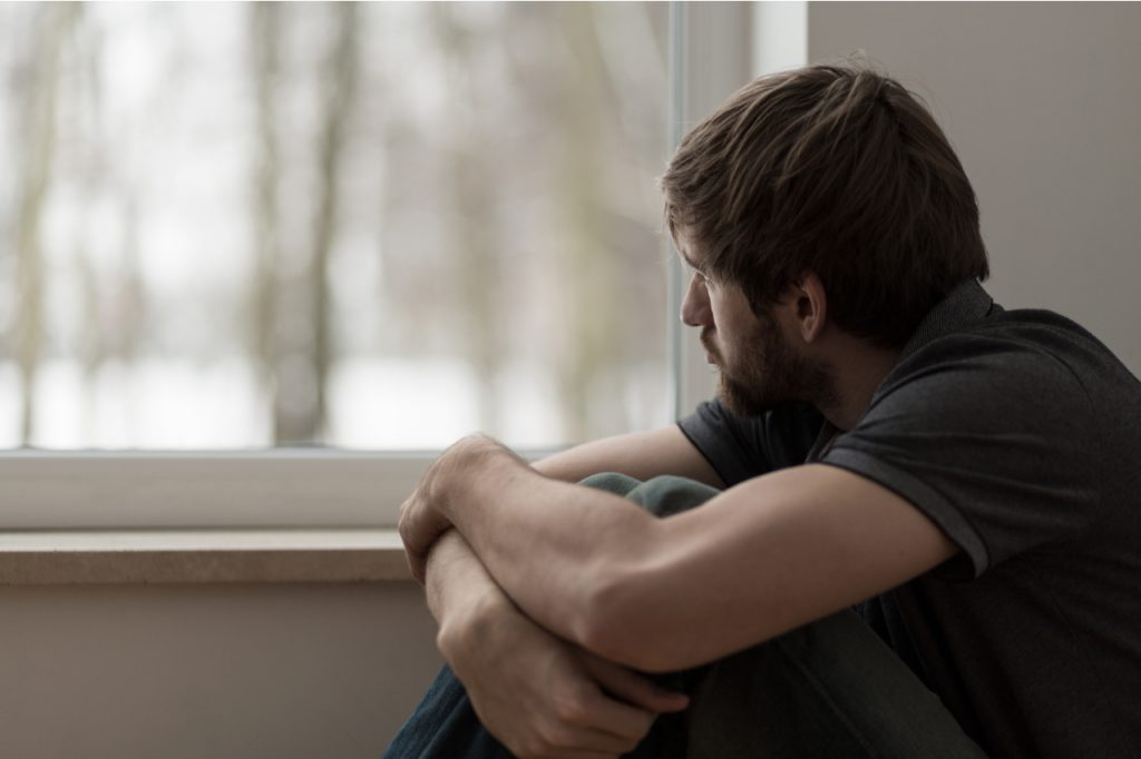 Depressed man sitting by the window.