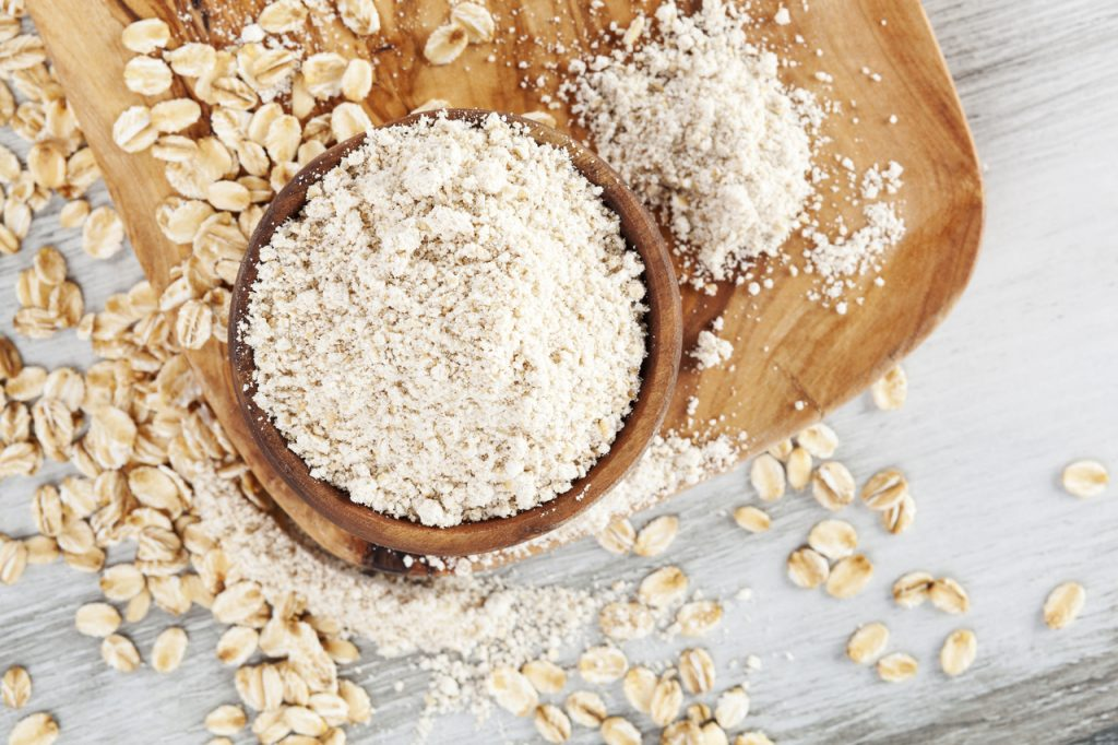 Oat wholegrain flour in bowl with oat flakes scattered on wooden table.