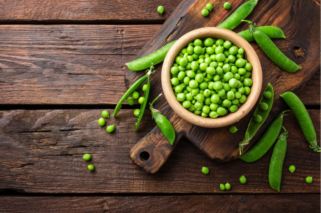 Green peas in a wooden bowl on a wooden chopping board.