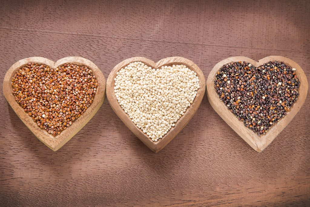 Complete-protein quinoa in three colors in heart-shaped wooden bowls.