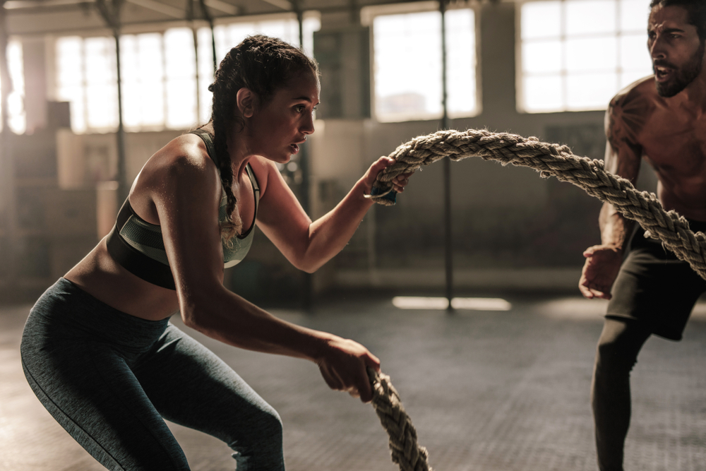 man training a woman with ropes in the gym