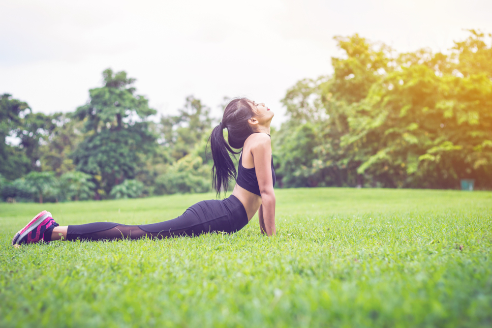 A woman doing yoga with nature as background.
