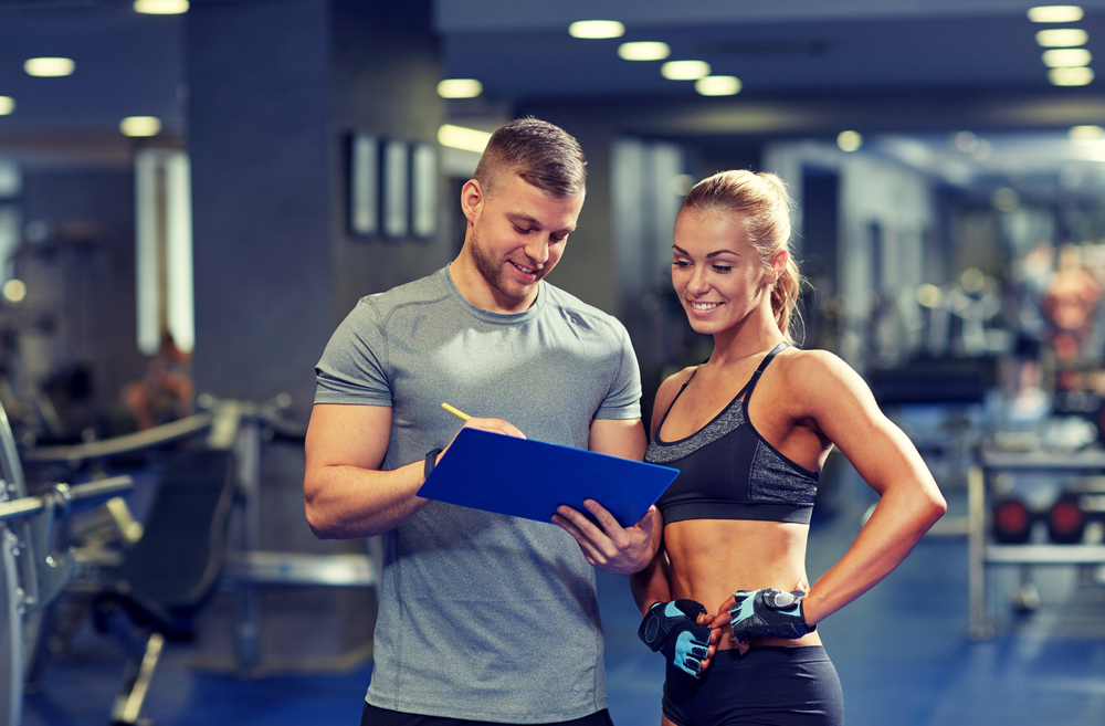 Man and woman writing down their workout goals for the new year
