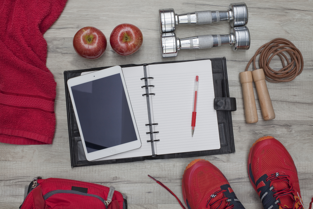 A workout journal, dumbells, jump rope, apples, sneakers and other tools for fulfilling your goals for the new year