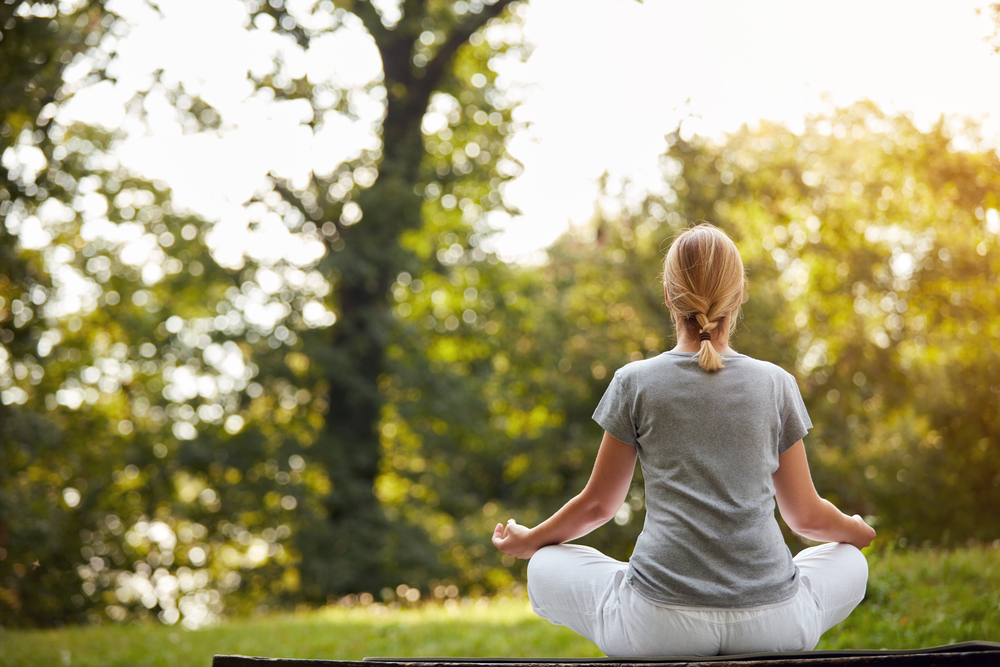 A woman meditating with nature as background.