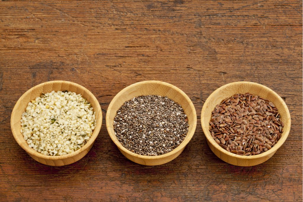 Chia seeds, flaxseeds, and hemp seeds in wodden bowls.