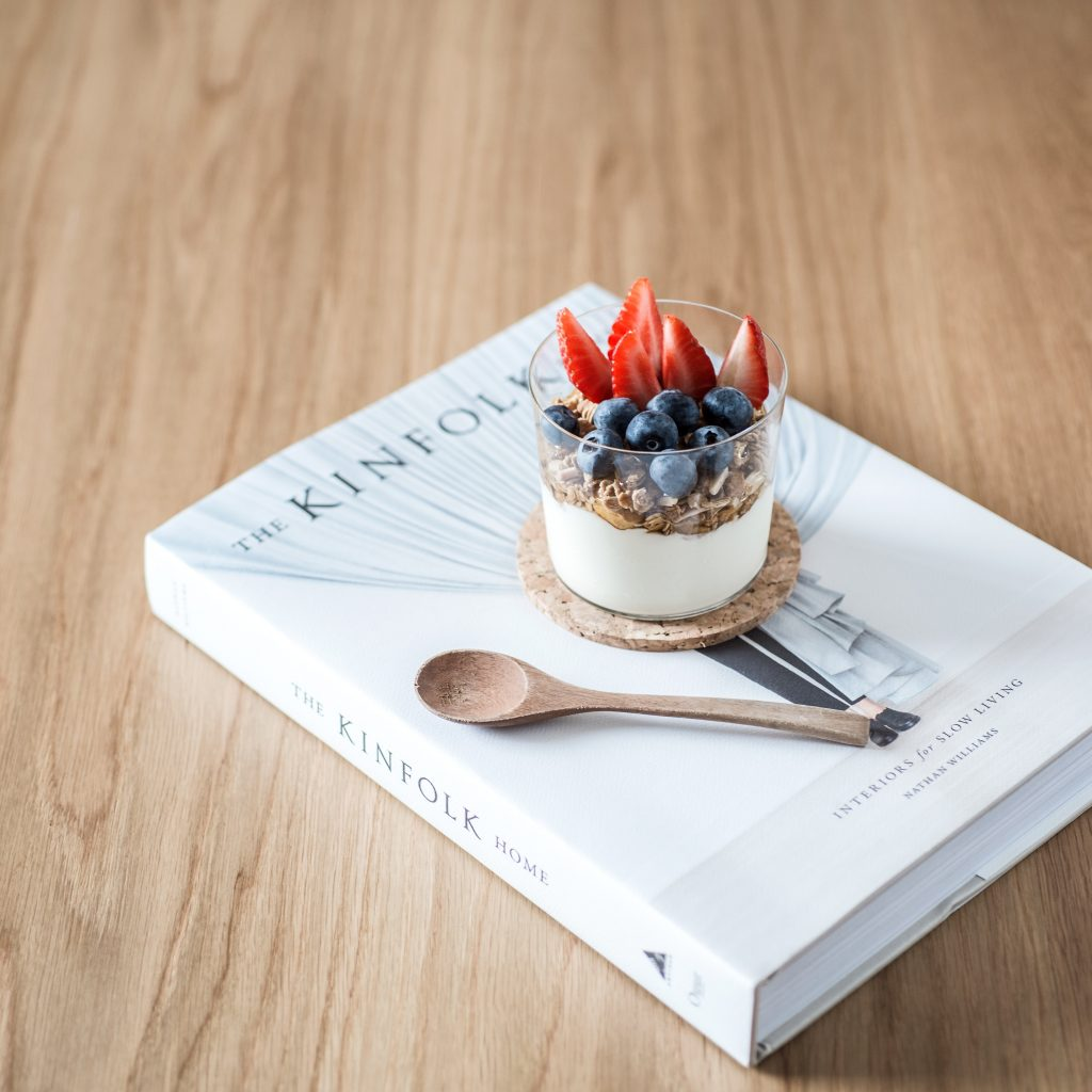 Yogurt in a glass on top of a book.
