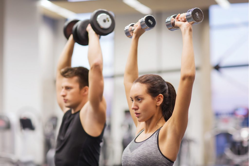 Man and woman lifting dumbbells at the gym.