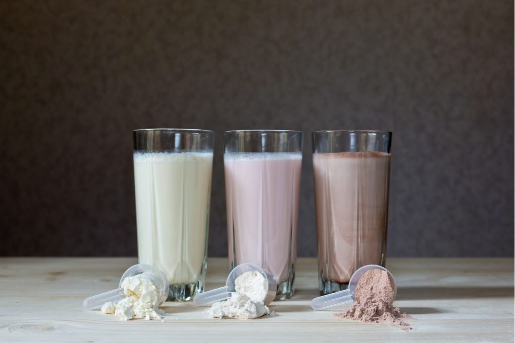 Three glasses of protein shakes with different flavors, vanilla, strawberry, and chocolate. Showing different types of protein powder.