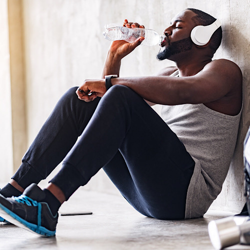 An African American man sitting on the floor while drinking water, wearing his headphones.