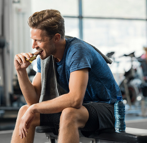 A man sitting on a bench in a gym while eating an energy bar.