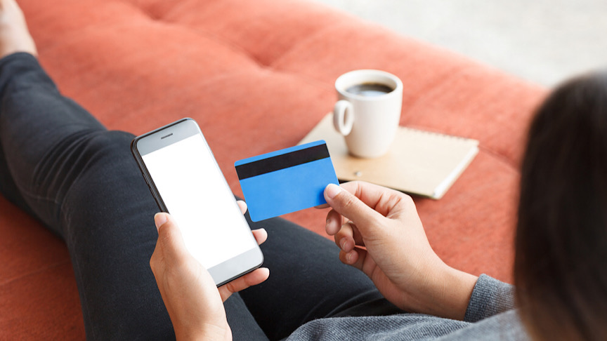 Woman holding iphone next to credit card.