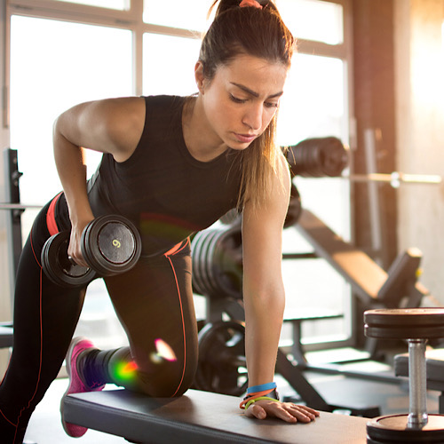 Woman doing rows with dumbell.