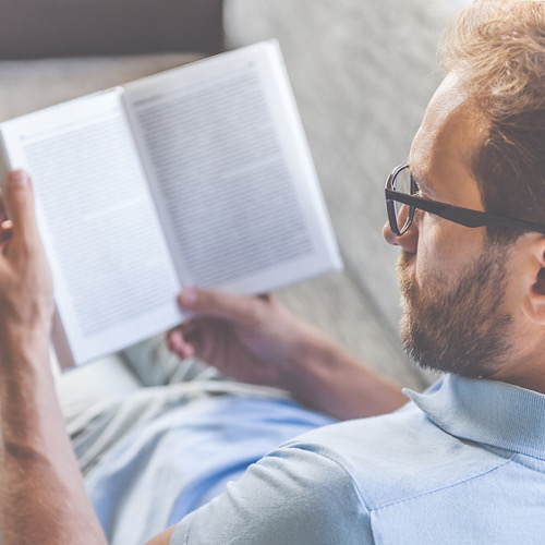 businessman in casual clothes and eyeglasses reading a book while lying on couch at home