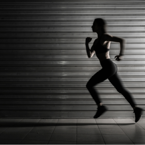 A silhouette of a fit woman running.