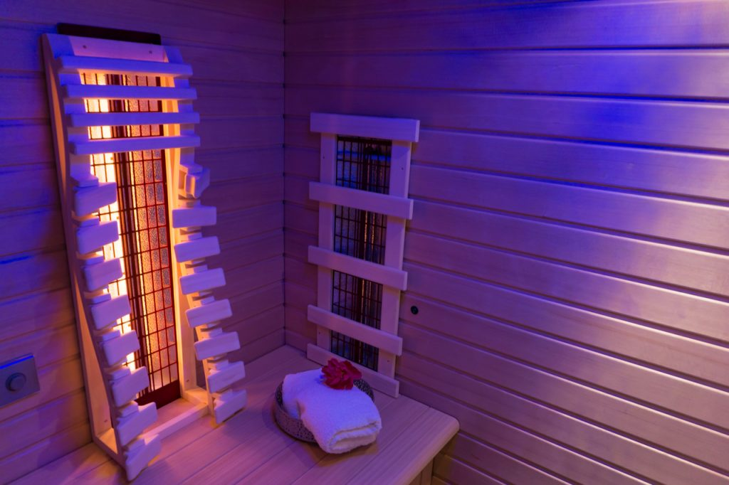 Feel the benefits of infrared sauna by looking at this image of an infrared sauna room in dim lighting.