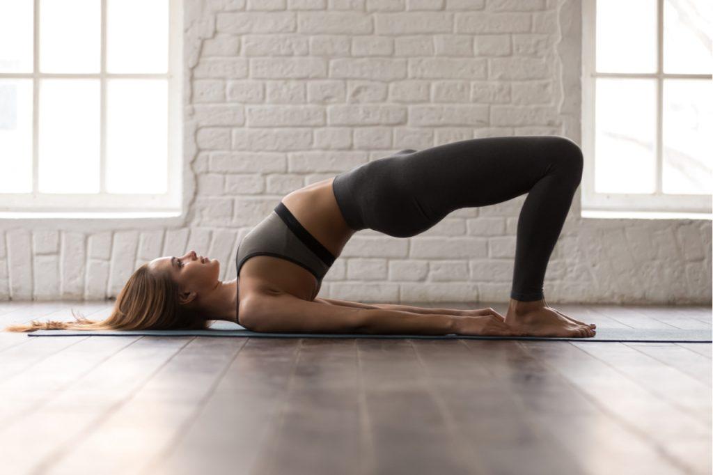 A woman doing the yoga bridge pose.