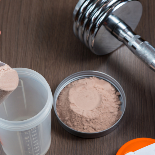 A woman ready to mix her casein protein powder to a shaker bottle next to a dumbbell.