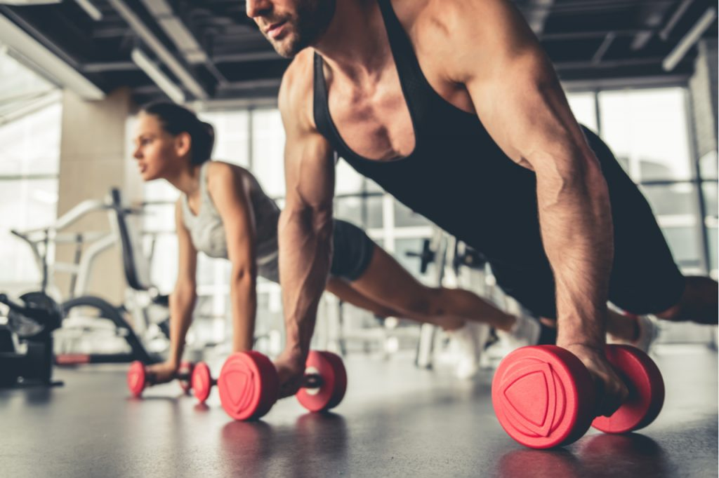 A man and woman doing a dumbbell exercise who will need tips on relief for muscle soreness.