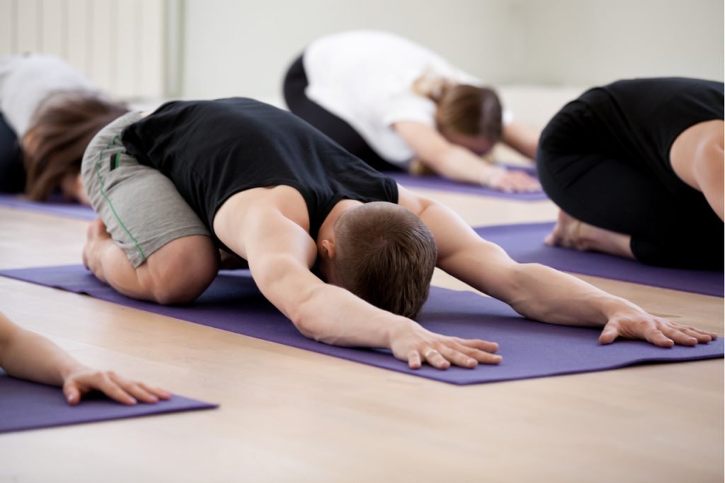 A man doing the child pose restorative yoga with a group.