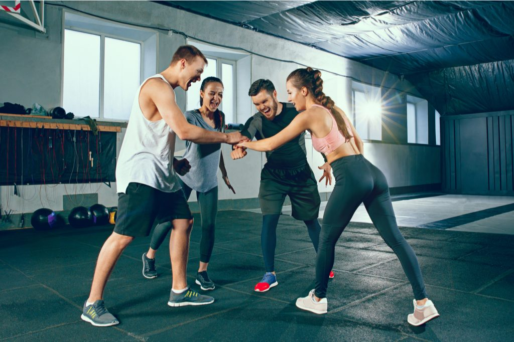 Group of friends ready to do a high-five to take on a challenging workout together.