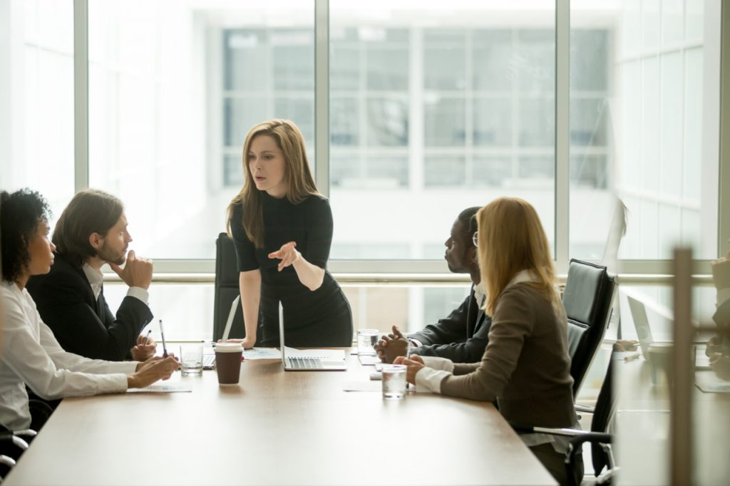 A woman delegating work to her employees.