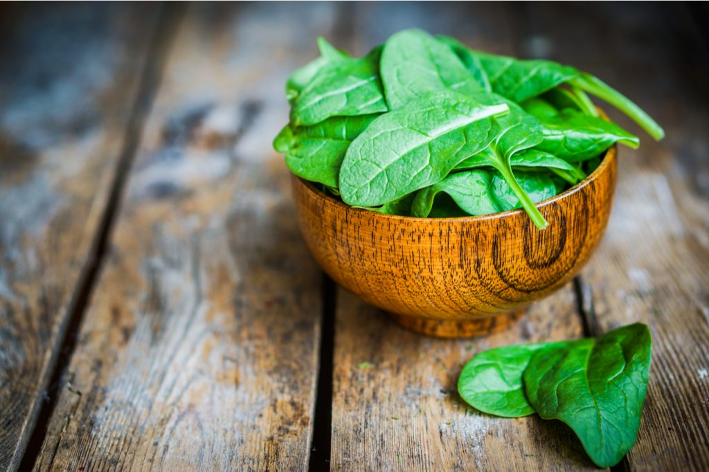 A bowl of fresh spinach in a wooden table.
