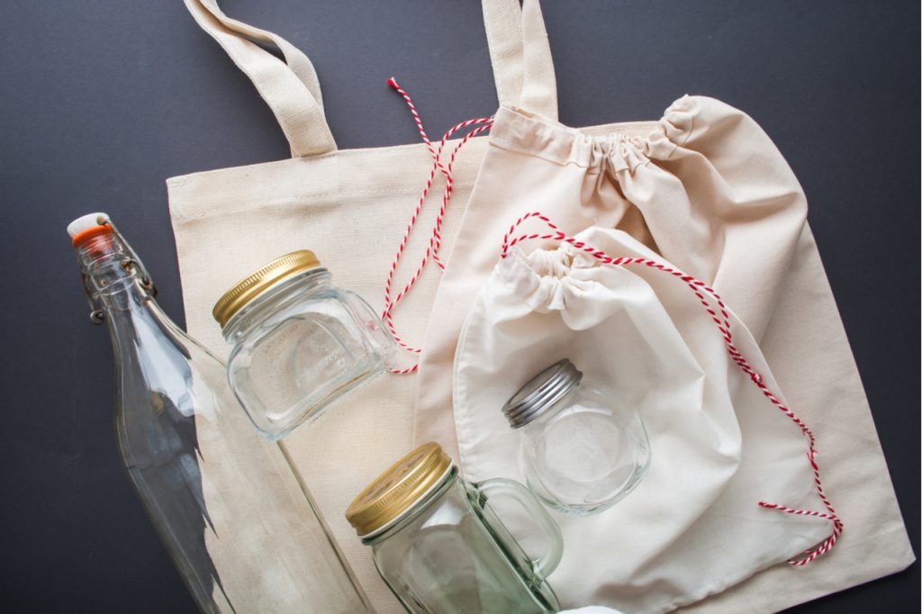 Cotton bags, glass jars and glass bottles for plastic-free shopping.
