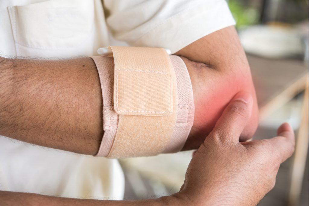 A man experiencing pain in his elbow needing an elbow bursitis treatment.