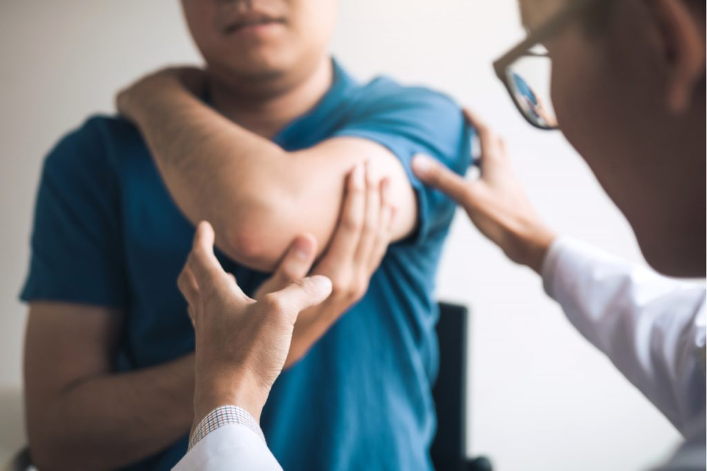 A man having his elbow checked by a physician.