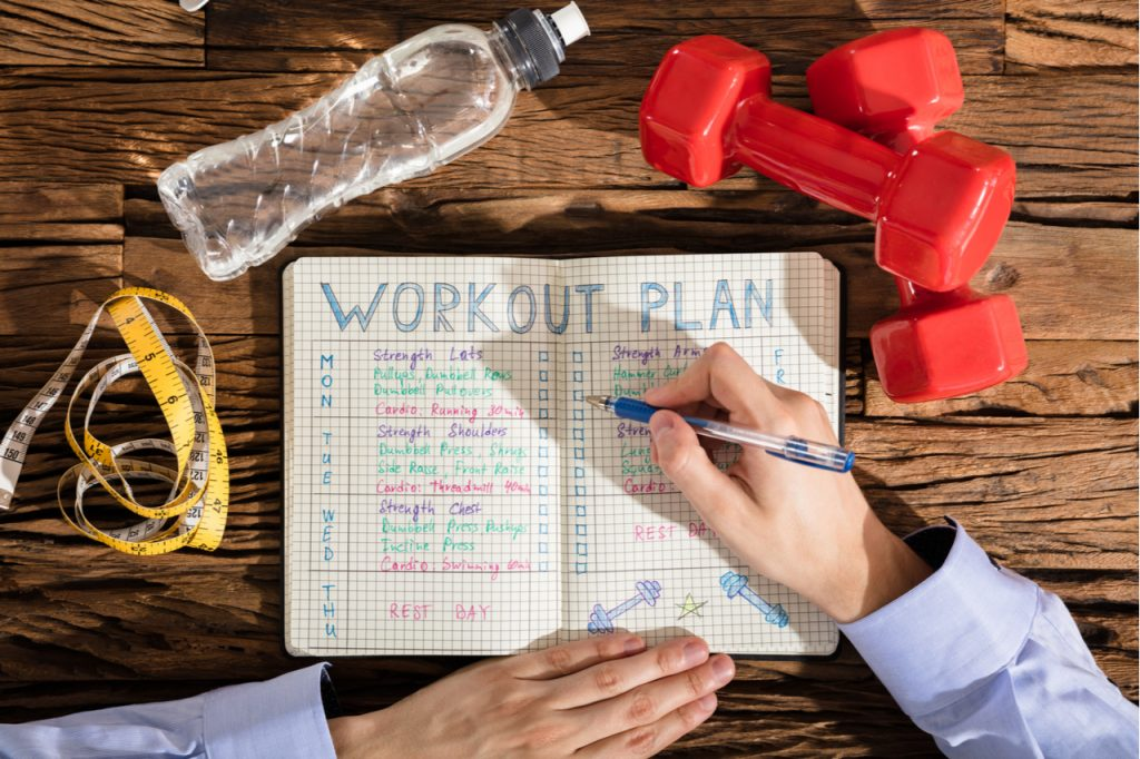 An image of a man making a workout plan wanting a long term fitness goal.