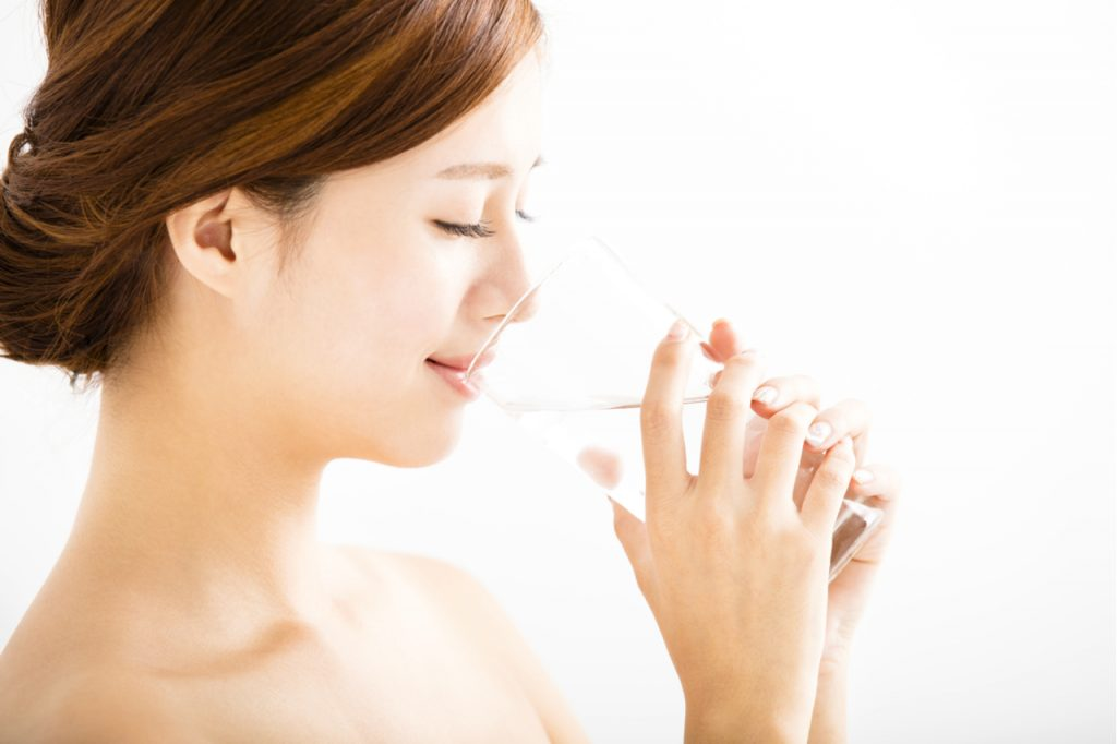 Woman with healthy looking skin drinking water from a glass.