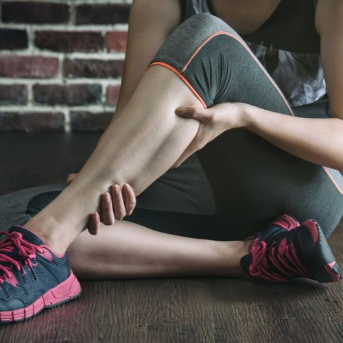 A woman experiencing leg muscle pain.
