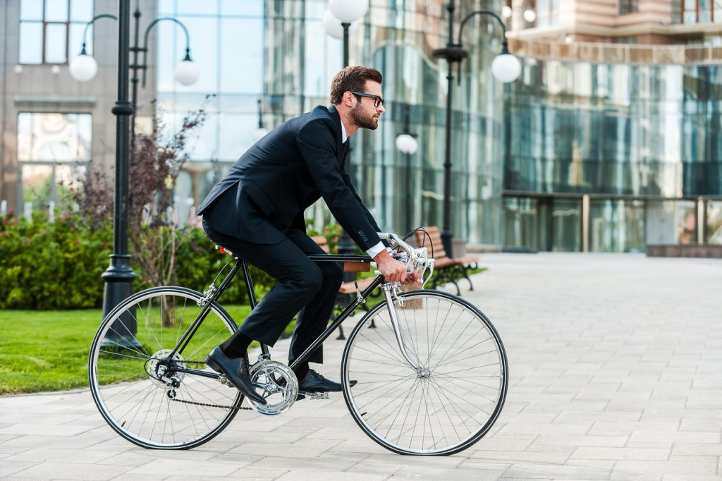 This man in suit riding his bike to work is an example of exercising environmental wellness.