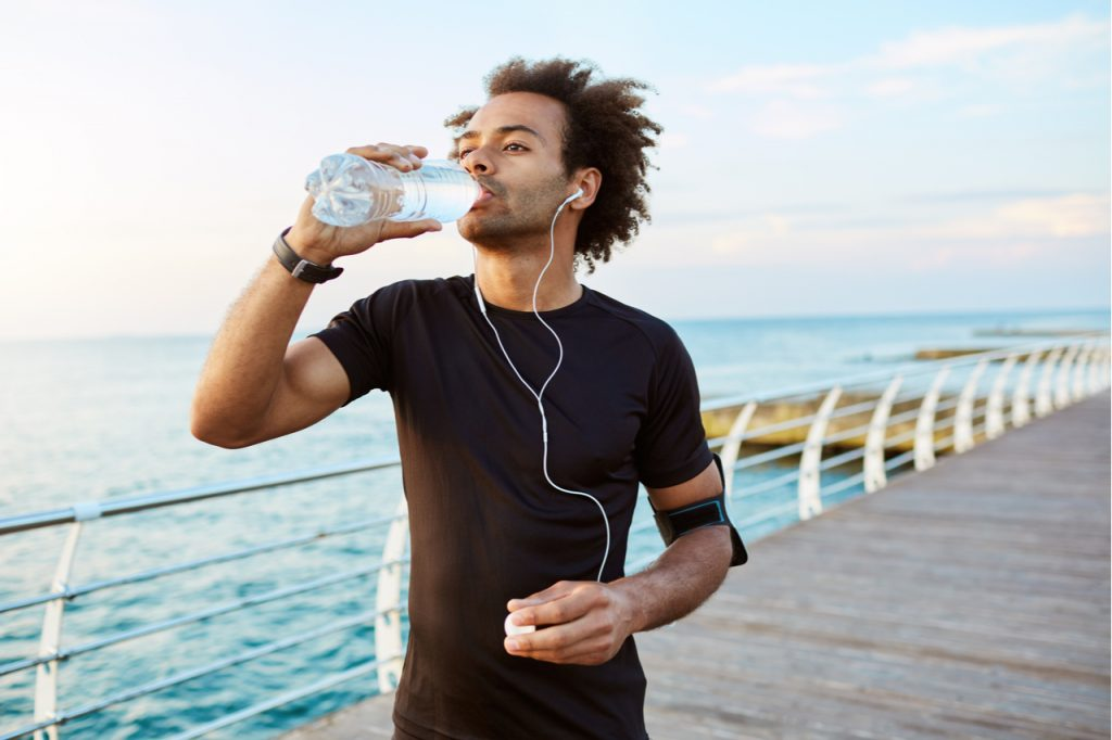 Man drinking water after jogging.  Hydration is just one of the many water benefits.