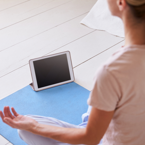 A woman meditating using a tablet.