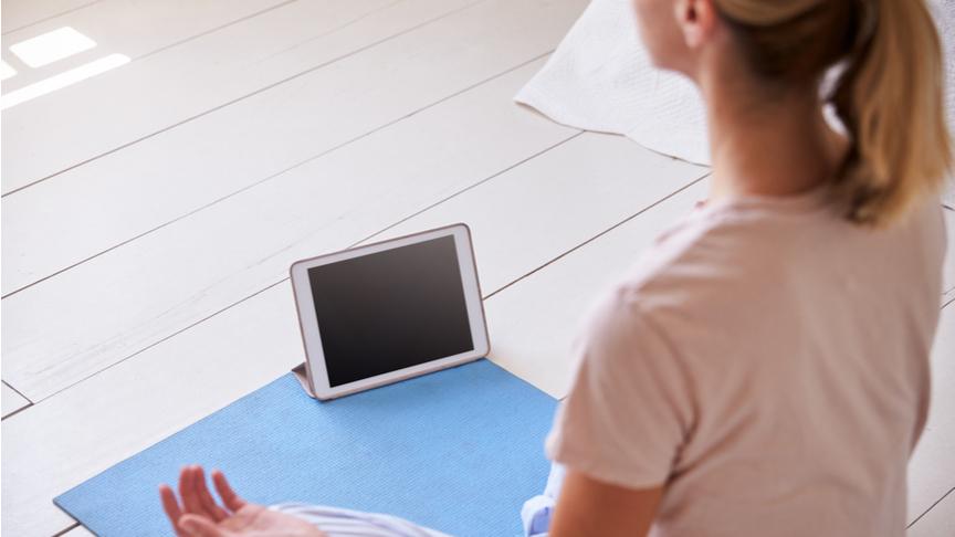 A woman meditating using a tablet.