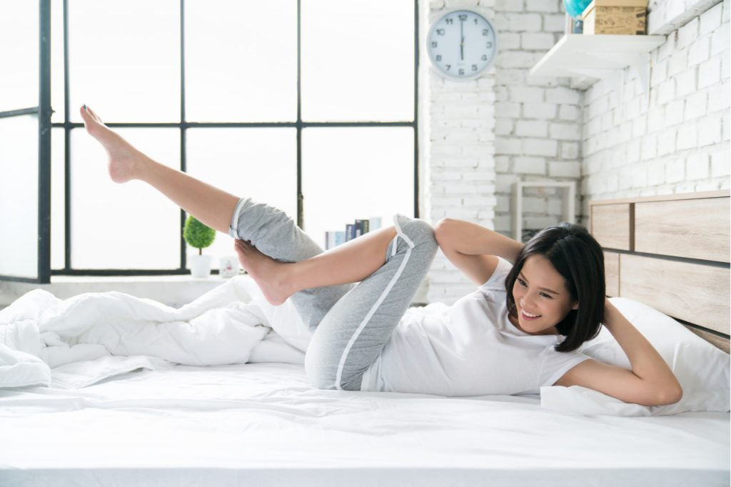 Woman exercising in bed, feeling refreshed.