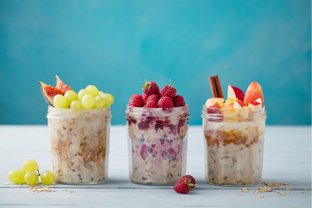 Three jars of overnight oats with grapes, berries and apples.