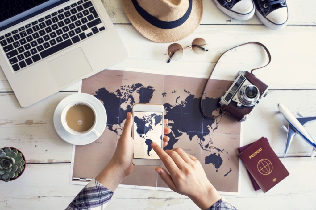 An image of a laptop, cup of coffee, sun glasses, pair of shoes, a hat, a camera, a model plane, 2 passport, a phone and a world map.
