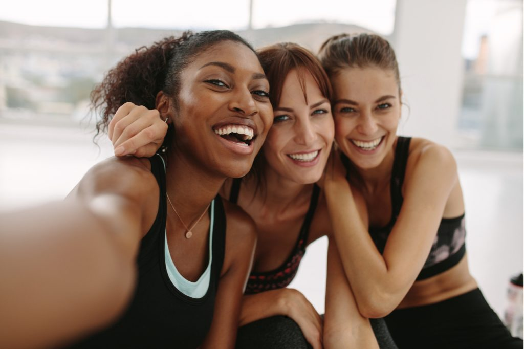 A multi racial group of women laughing together and enjoying the moment.