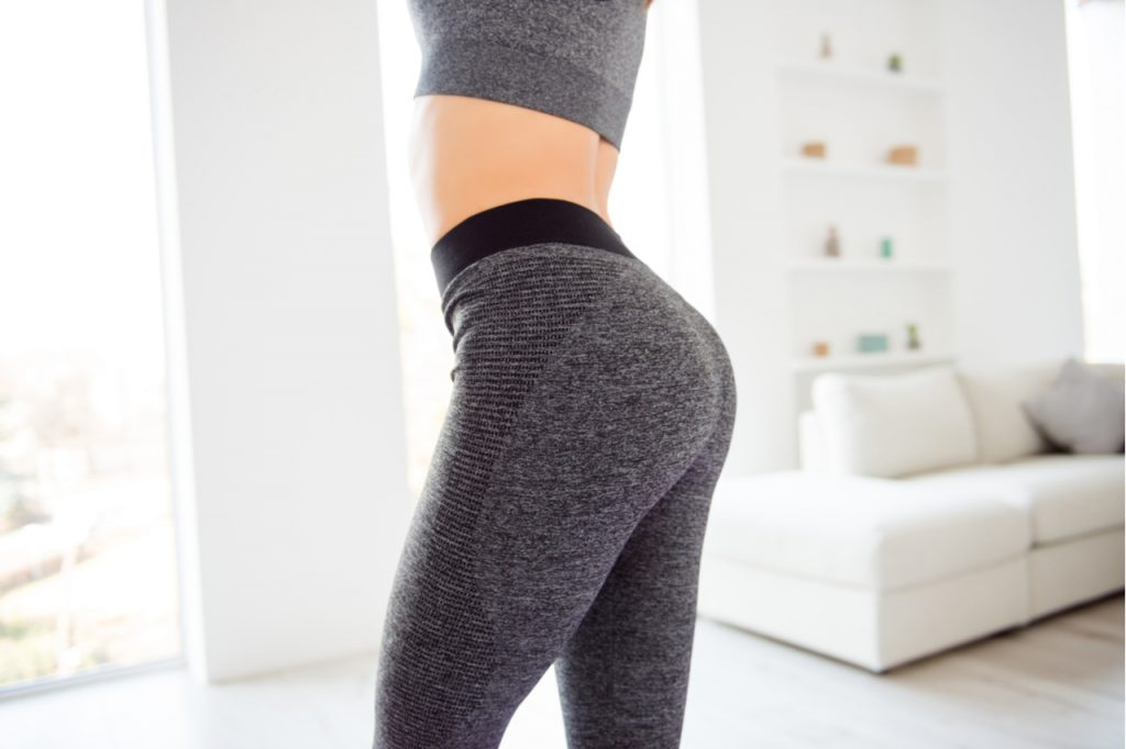 Cropped photo of a sexy woman with a round shaped butt wearing gray tight leggings.