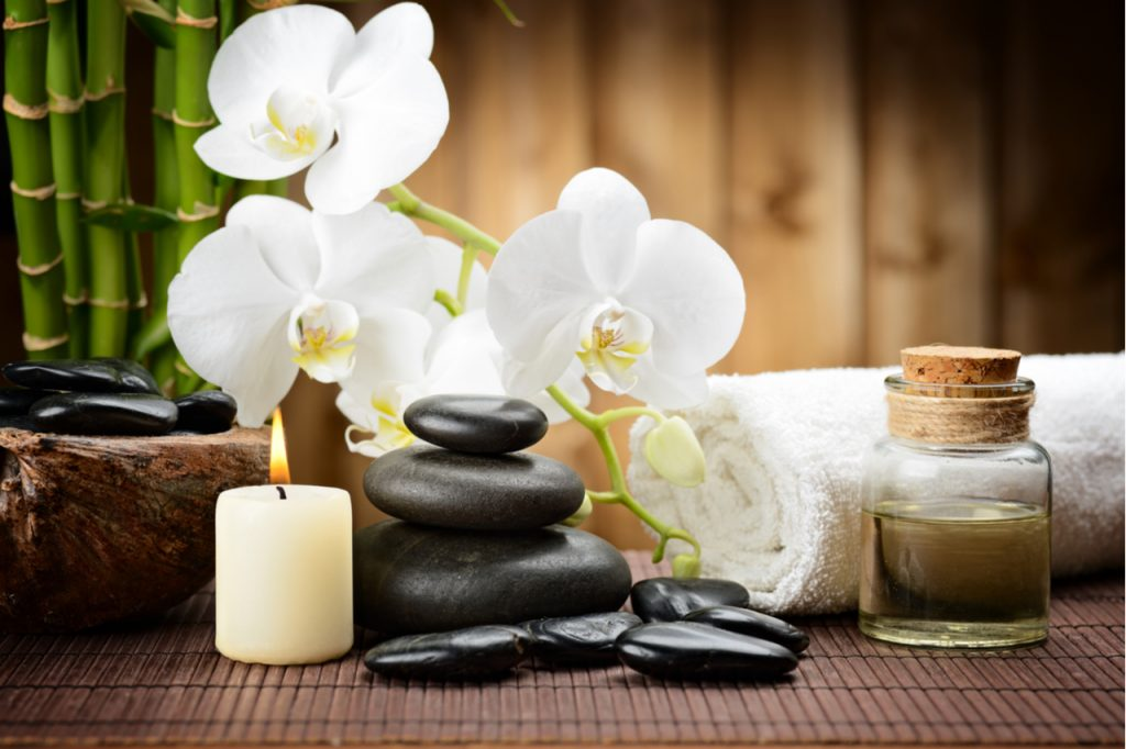 Stone, essential oil, a towel, a flower and a candle light.