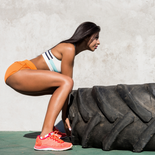 A fit woman doing tire exercise.