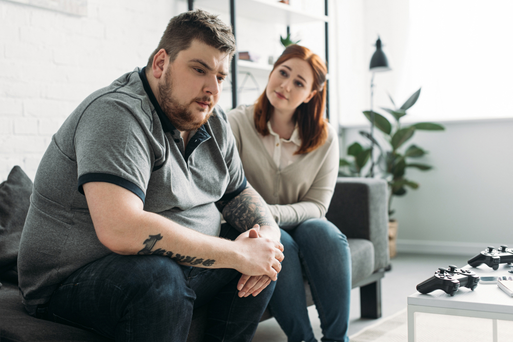 An obese man looking sad while sitting with his girlfriend.