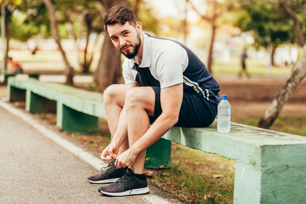 Man sitting on a bench while tying his shoe lace.